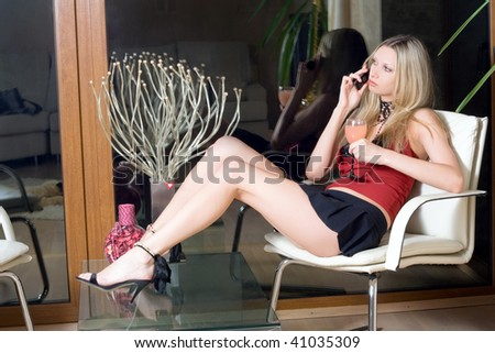 Attractive blond woman with a glass of cocktail speaking on the phone - stock photo