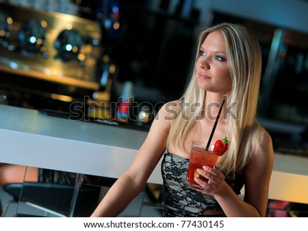 attractive blond woman with cocktail drink sitting in bar - stock photo