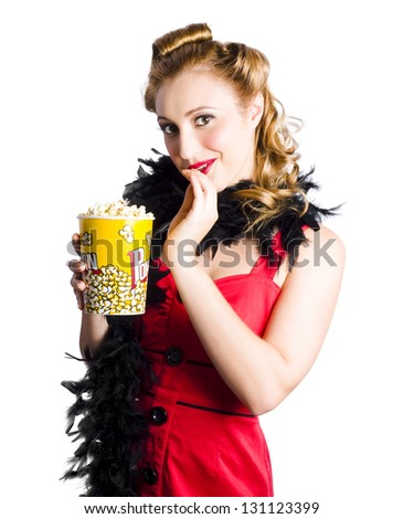 Attractive blond woman with curls in red dress and black stole holding a large carton of popcorn on white background - stock photo