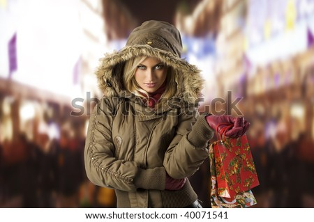attractive blond woman with shopping bag covering her head with hood from winter - stock photo