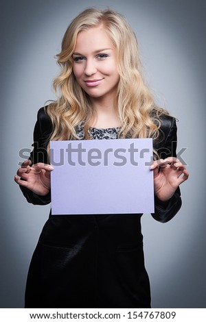 Attractive blond women holding a blank paper notice. - stock photo