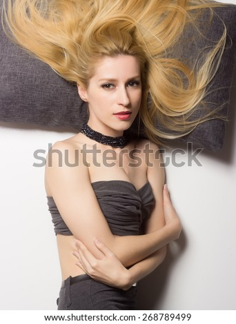 Attractive blond women in 30's laying on pillows.