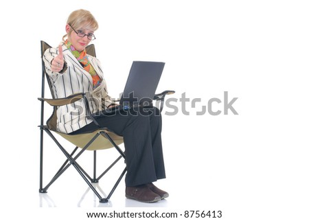 Attractive blond young businesswoman in director chair, pensive look, working on laptop.  White background, studio shot.
