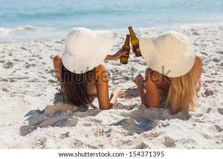 Attractive blonde and brunette with straw hats and bikinis clinking glass bottles - stock photo