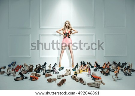 Attractive blonde beauty next to many pairs of high heel shoes