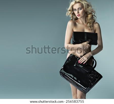 Attractive blonde beauty with elegant handbags  - stock photo