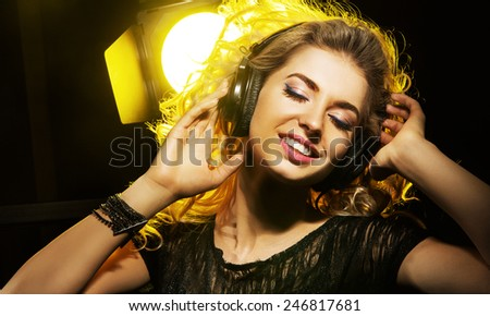 Attractive blonde beauty with headphones - stock photo