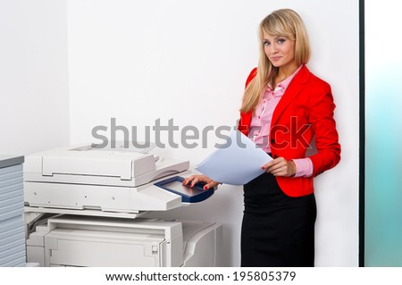 attractive blonde business woman with documents standing next to office printer - stock photo