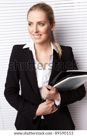 Attractive Blonde Businesswoman clasping a file and standing in front of a white blind, upper body - stock photo