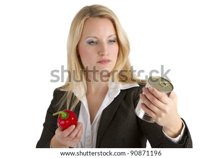 Attractive blonde businesswoman holding a red papper and unlabelled tin can while comparing fresh and tinned vegetables.