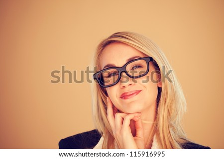 Attractive blonde businesswoman in glasses beaming with pleasure on a light brown background with copyspace