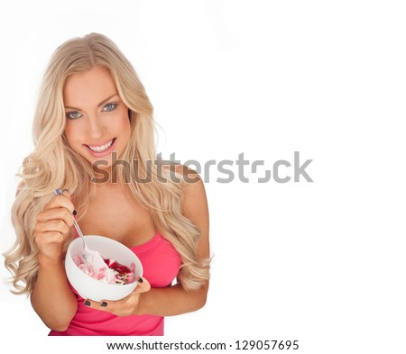 Attractive blonde Caucasian fit young woman eating ice cream from a ceramic bowl - stock photo