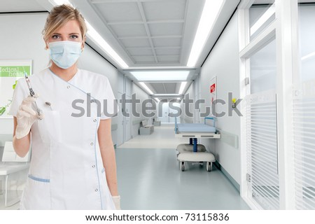 Attractive blonde female dentist holding a syringe in a clinic interior