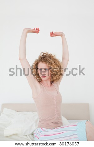 Attractive blonde female stretching in her bedroom in her apartment - stock photo