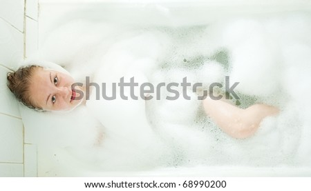 Attractive blonde girl enjoys in the bath - stock photo