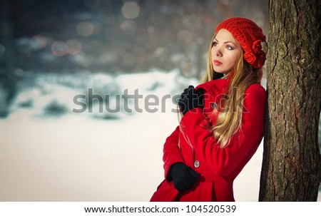 Attractive blonde girl with gloves, red coat and red hat posing winter snow - stock photo