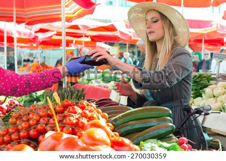 Attractive blonde girl with straw hat buying vegetables on  marketplace. - stock photo