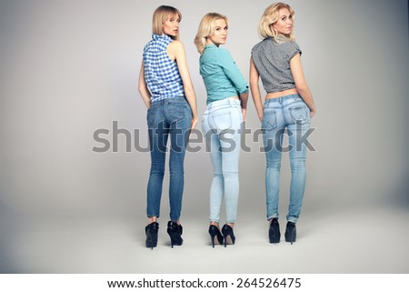 Attractive blonde girls posing in studio, wearing fashionable jeans. - stock photo