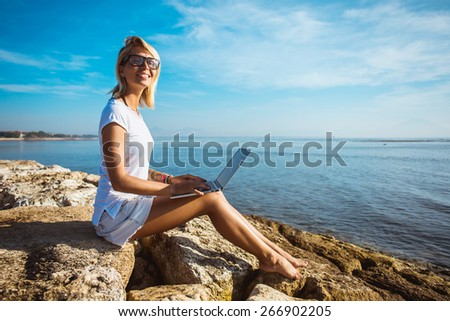 Attractive blonde hair woman working with a laptop on the seashore and look to the camera. Female freelancer working near the sea. - stock photo