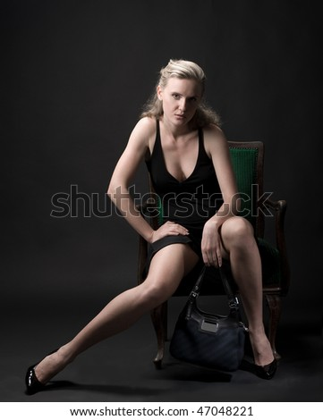 attractive blonde in dress sitting in a chair on a black background