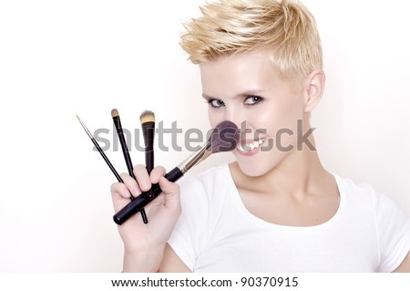 Attractive blonde Make-up artist holding brushes - stock photo