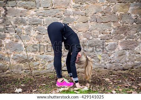 Attractive blonde middle aged woman stretching her body in front of ancient wall in park