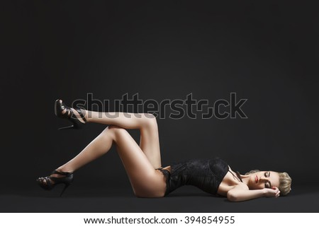 Attractive blonde model posing in black lace lingerie on ground in studio wearing high heels - stock photo