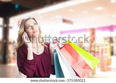 Attractive blonde on shopping in shop using a cellphone - stock photo