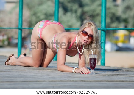 Attractive blonde on the beach. Young woman in swimwear is posing on open air. - stock photo
