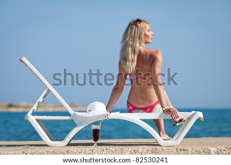 Attractive blonde on the beach. Young woman in swimwear is posing on open air.