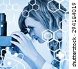 Attractive blonde scientist looking through a microscope against science graphic - stock photo