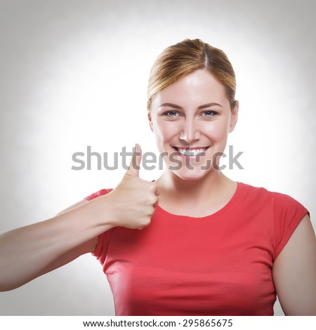 Attractive blonde showing thumbs up. Toned photo. - stock photo