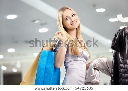 Attractive blonde smiles in outer clothing shop - stock photo