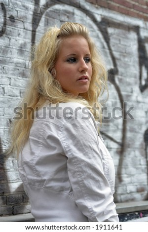 Attractive blonde standing against a brick wall with graffiti