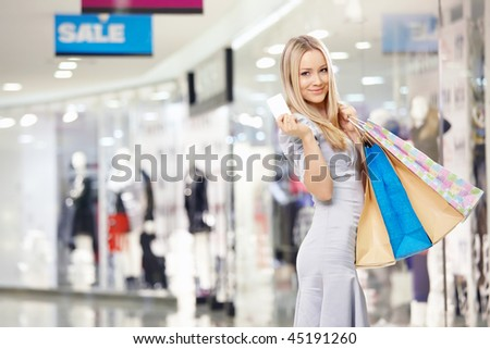 Attractive blonde with bags and a credit card in shop - stock photo