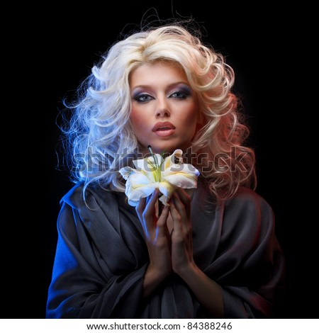 Attractive blonde with blue eyes wearing gray silk dress holding white lily by both hands on black background - stock photo