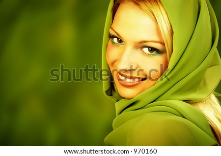 Attractive blonde with lovely makeup on green background. Great pic for advertising.