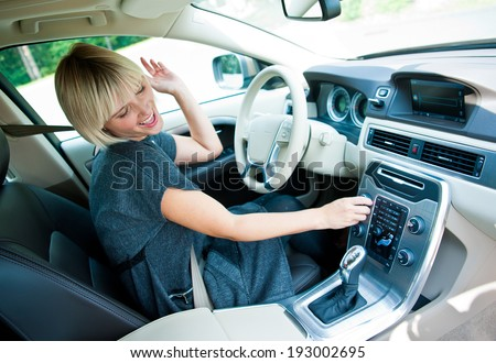 attractive blonde woman changing radio station in her car - stock photo