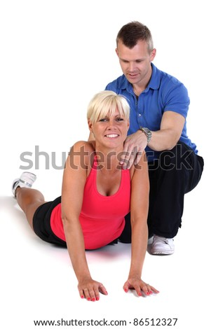Attractive blonde woman doing exercises with the support of her fitness coach. - stock photo