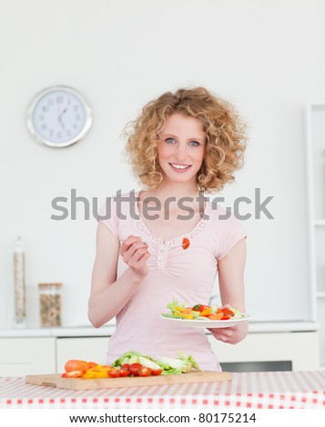 Attractive blonde woman eating some vegetables in the kitchen in her apartment - stock photo