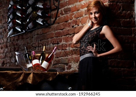 Attractive blonde woman in elegant black dress sitting on bar stool. Gorgeous blonde model posing provocatively in vintage bar .Fashion colors. - stock photo