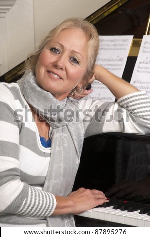Attractive blonde woman in her 50's leaning against a grand piano.