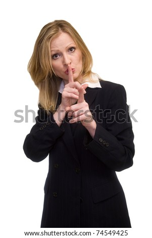Attractive blonde woman in professional business suit standing on white with one finger over lips and the other pointing forward looking directly into the lens - stock photo