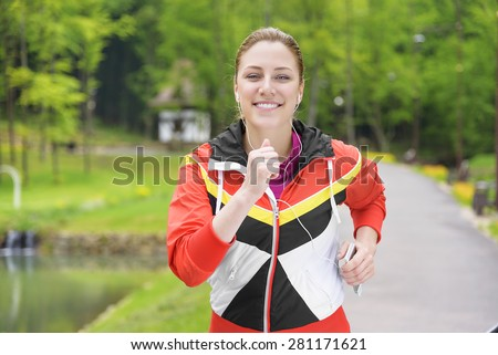 Attractive blonde woman jogging and listening to the player. - stock photo