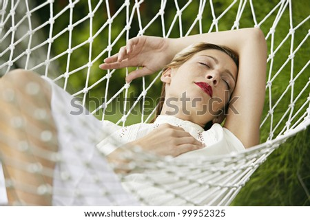 Attractive blonde woman laying down on a white hammock, sleeping and wearing red lipstick. - stock photo