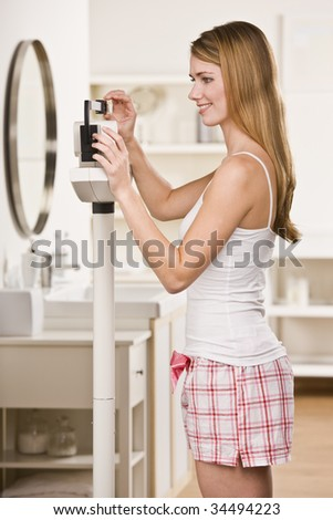 Attractive blonde woman on scale, weighing herself and smiling. Not looking at camera. Vertical