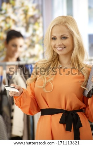 Attractive blonde woman paying by credit card at clothes store, smiling happy.