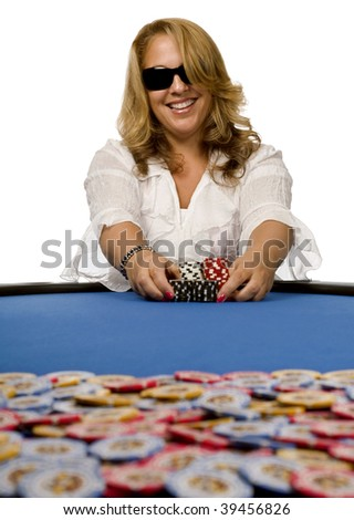 Attractive blonde woman pushes poker chips towards pot on blue felt table. - stock photo