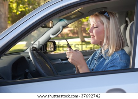 Attractive Blonde Woman Text Messaging on Her Cell Phone While Driving. - stock photo