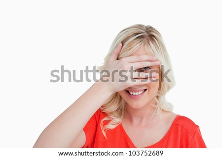 Attractive blonde woman trying to see through her fingers placed in front of her face - stock photo
